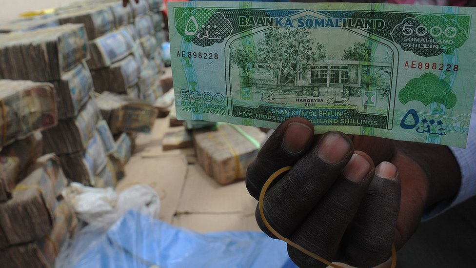 A man holds a 5,000-Somaliland shilling banknote.