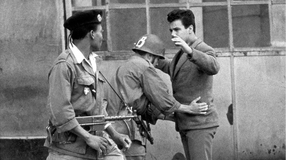 French troops frisk an Algerian during the independence struggle