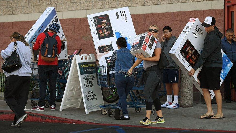 Compradores con grandes cajas de televisores.
