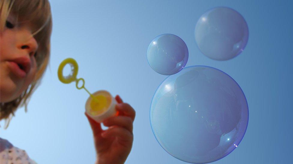 Una niña haciendo burbujas de jabón