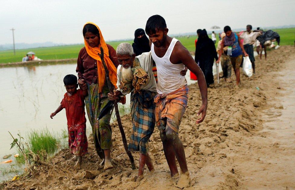 people helping an old man through mud