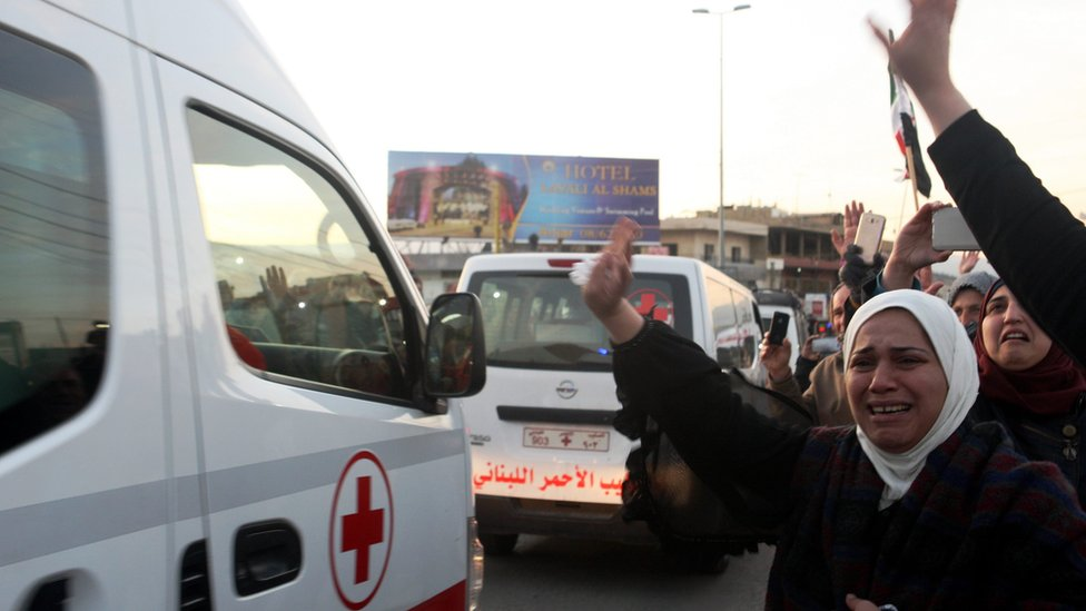 Syrian refugees wave to convoy of ambulances that evacuate wounded people from the rebel-held town of Zabadani, Syria, crossing the Lebanese border at Masnaa east of Lebanon (28 December 2015)