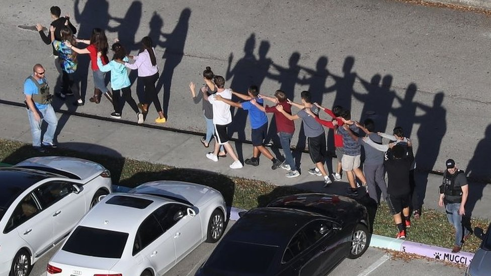 People are brought out of the Marjory Stoneman Douglas High School after a shooting.