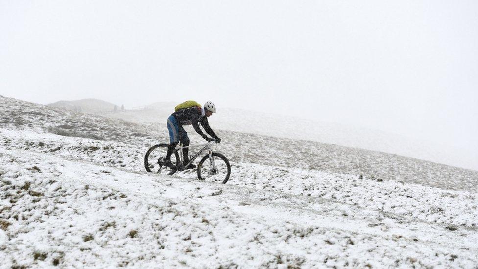 رجل يقود دراجته عبر الثلوج على تلال منطقة بيك دستريكت