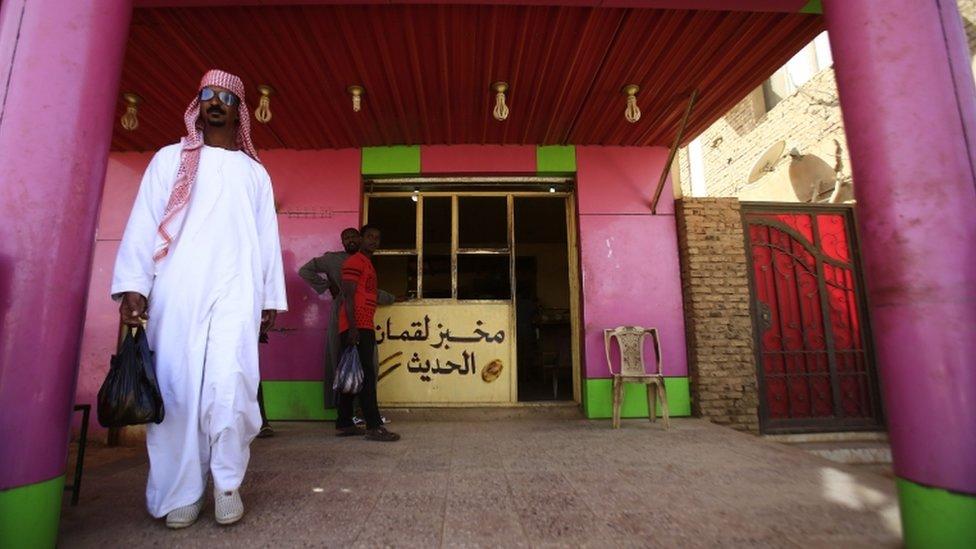 رجل سوداني يغادر مخبزا وهو محمل بحقيبة مملوءة بقطع الخبز في العاصمة السودانية، الخرطوم.