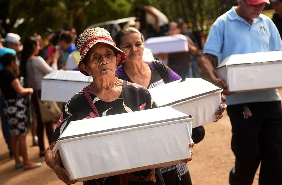 Mujeres cargan ataúdes con las víctimas de la masacre de El Mozote, en El Salvador.