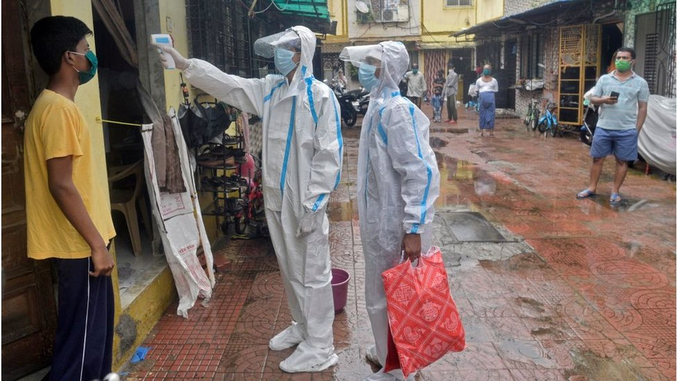 Health care staff check the temperature of a Mumbai resident