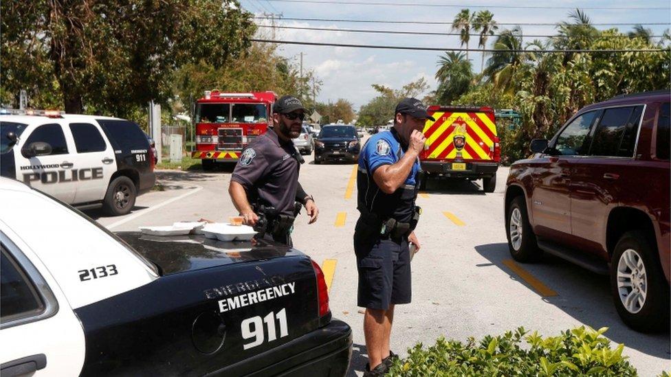 Dos agentes junto al cordón policial en torno al edificio en que se registraron las muertes.