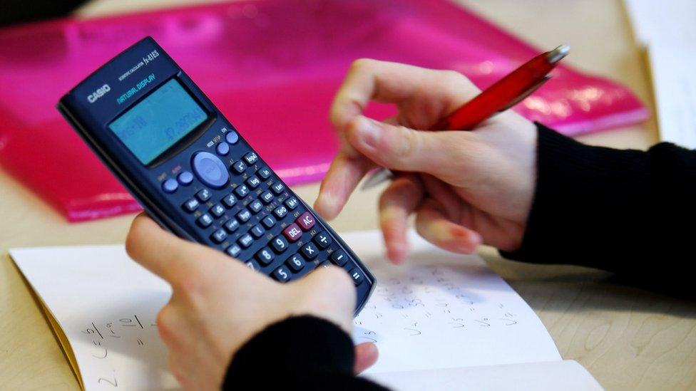 Estudiante sujetando una calculadora