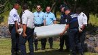 French gendarmes and police inspect a large piece of plane debris found on the beach in Saint-Andre, on the French Indian Ocean island of La Reunion