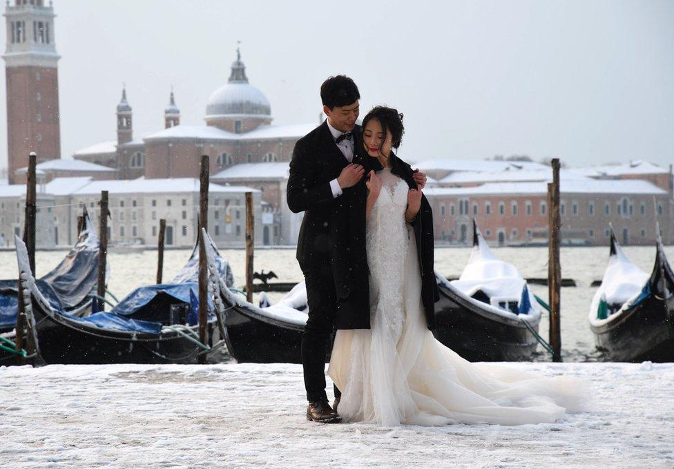 زوجان يلتقطان صور زفاف في ميدان القديس مرقس بمدينة البندقية في إيطاليا في أعقاب هطول الثلوج خلال الليل.