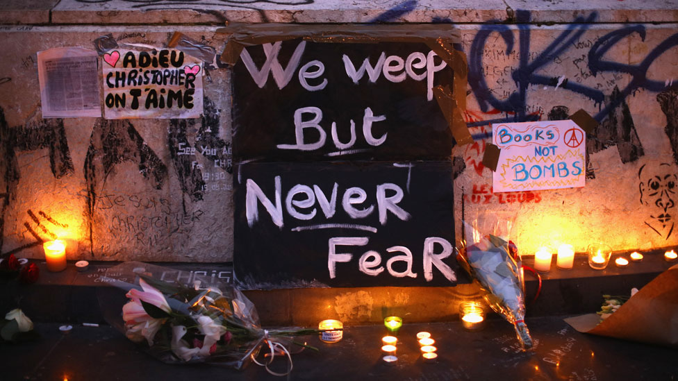 "A vigil in Paris with a sign reading ""We weep but never fear"""