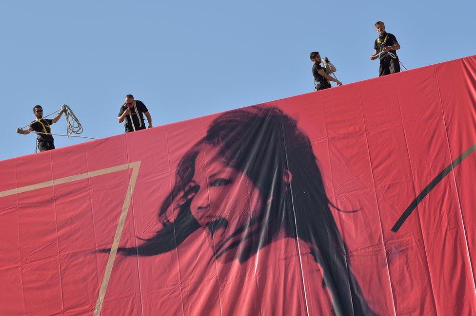 Personas trabajan para instalar un poster en el festival de Cannnes
