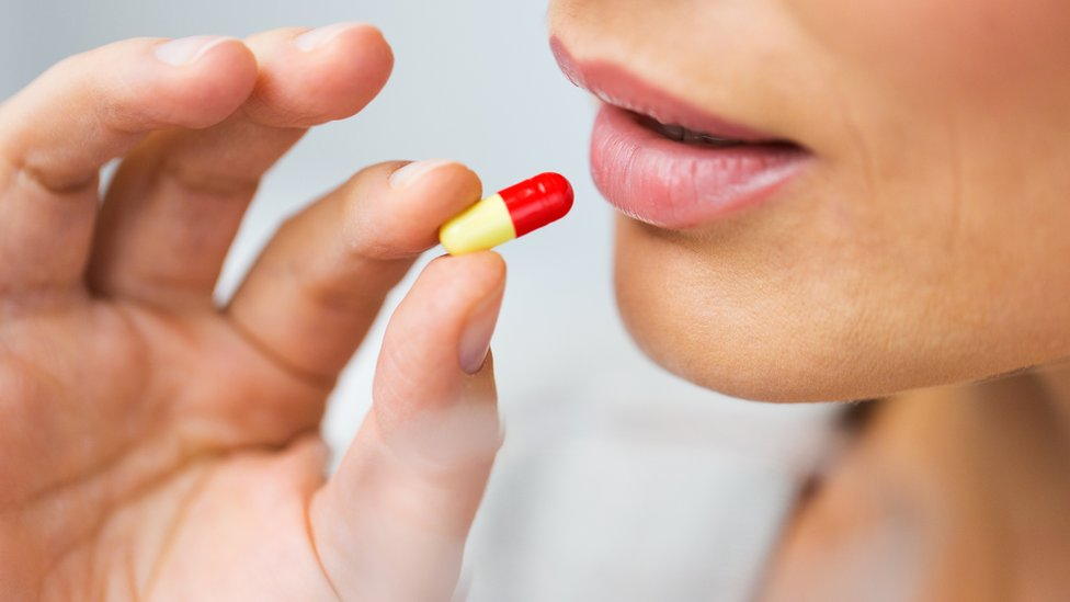 Mujer ingiriendo una píldora.