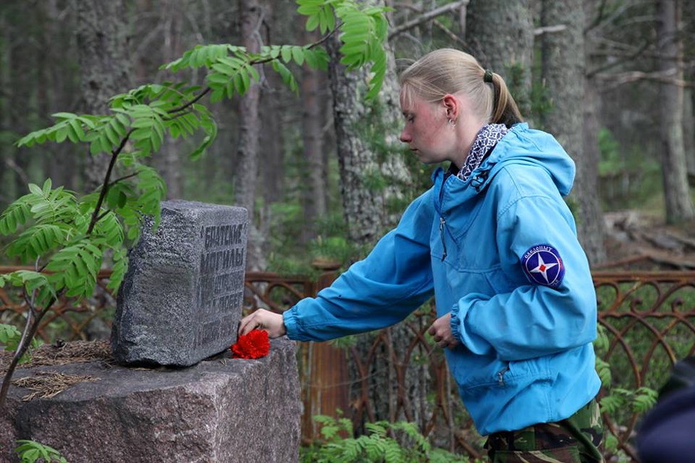 Marina Titova coloca un clavel frente a una lápida en la isla de Mudyug (Foto: Aleksey Suhanovsky)
