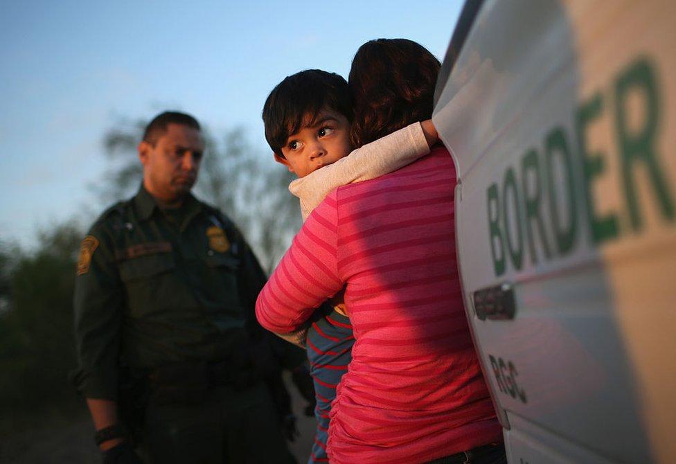 Un niño de un año se agarra al cuello de su madre salvadoreña, quien acaba de cruzar de forma ilegal la frontera entre México y Estados Unidos ante la atenta mirada de un agente de la guardia fronteriza cerca de Río Grande, Texas, el 7 de diciembre de 2015.
