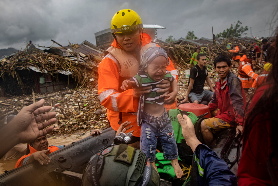 A rescuer carries a baby as floodwaters rise in a submerged village