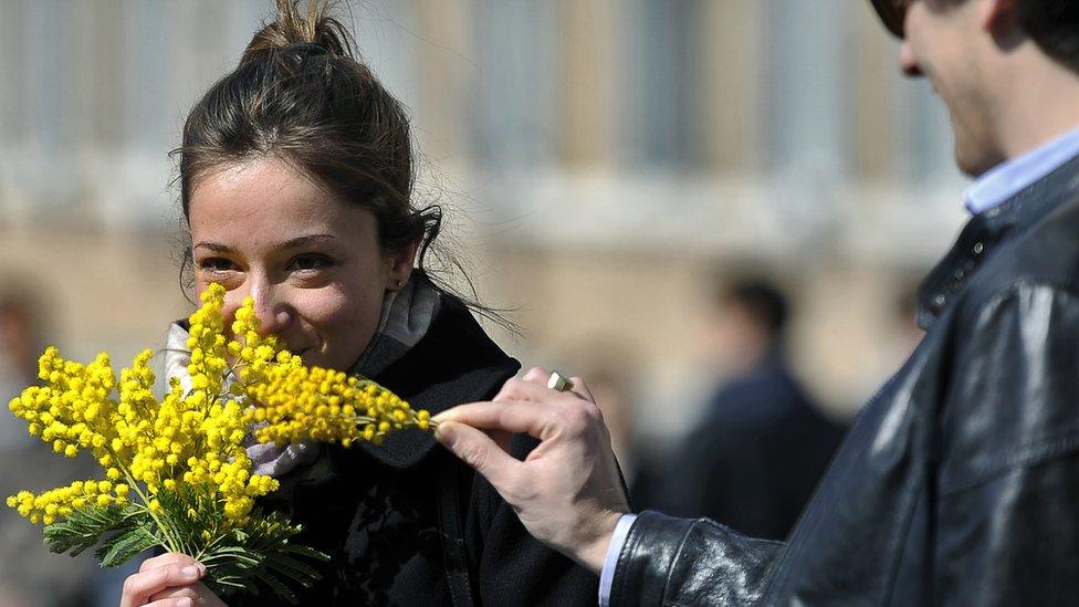 امرأة تحمل حفنة من أزهار الميموسا في روما في اليوم العالمي للمرأة 2012