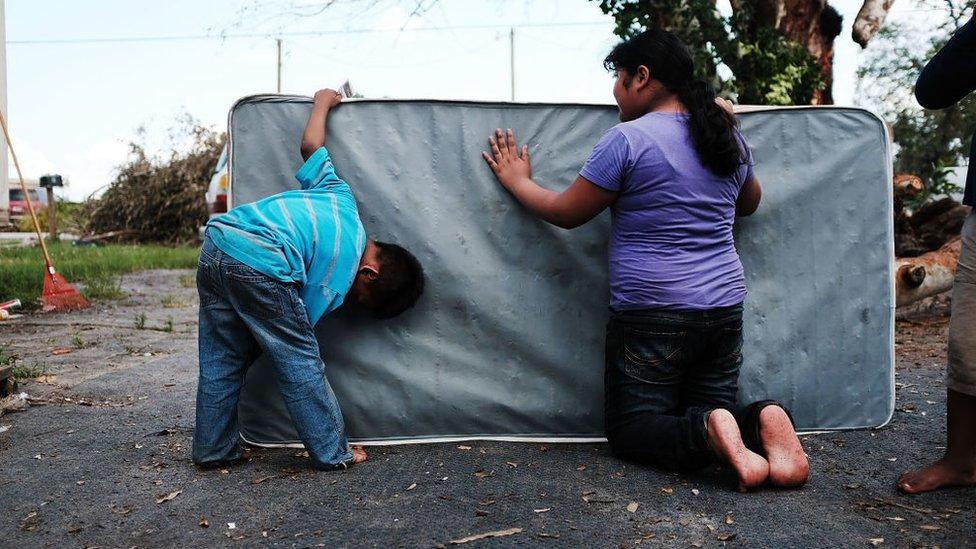 Dos niños limpian un colchón que se ensució por las inundaciones.