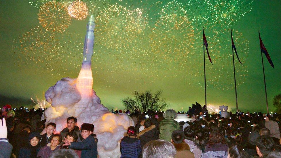 平壤民眾在新年的焰火下與洲際彈道導彈冰雕合影