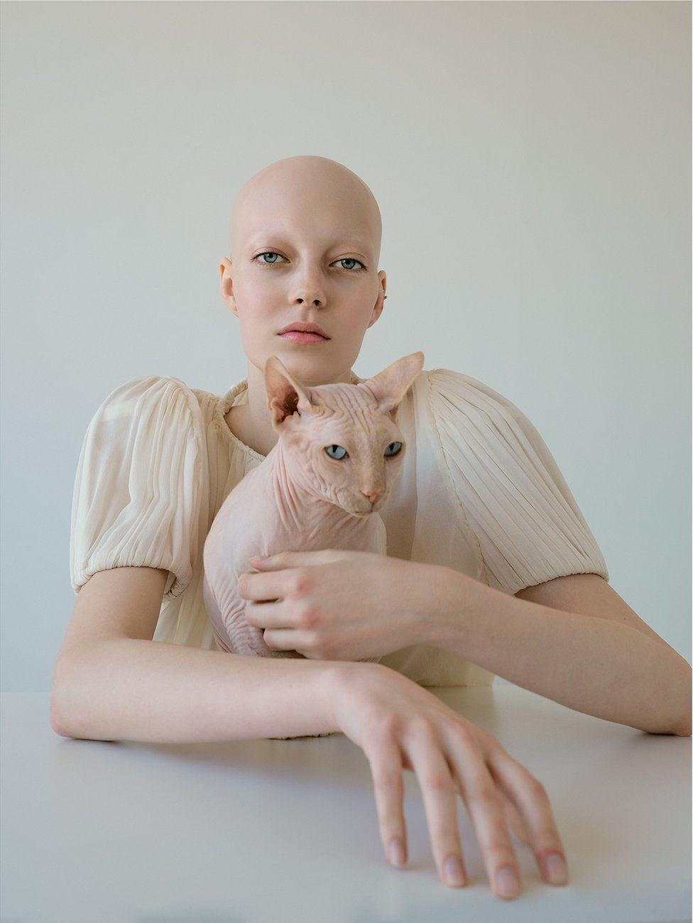 A young woman without hair holds a bald cat