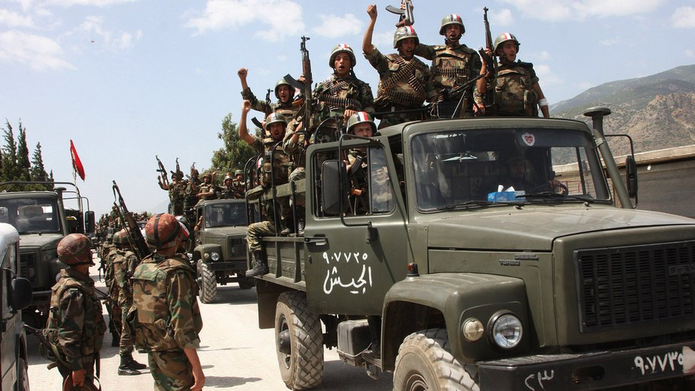 Syrian army soldiers standing on their military trucks chant slogans in support of President Bashar al-Assad, as they enter a village near the town of Jisr al-Shughour (10 June 2011)