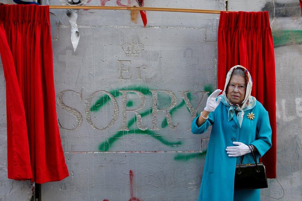Un actor disfrazado de la reina Isabel II de Inglaterra durante un evento por el aniversario número 100 de la Declaración Balfour, afuera del Walled Off Hotel, de Banksy, en Belén.