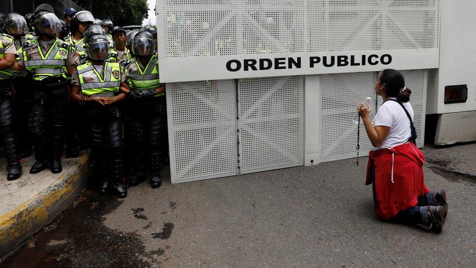 Una manifestante opositora se arrodilla frente a un contingente de la policía