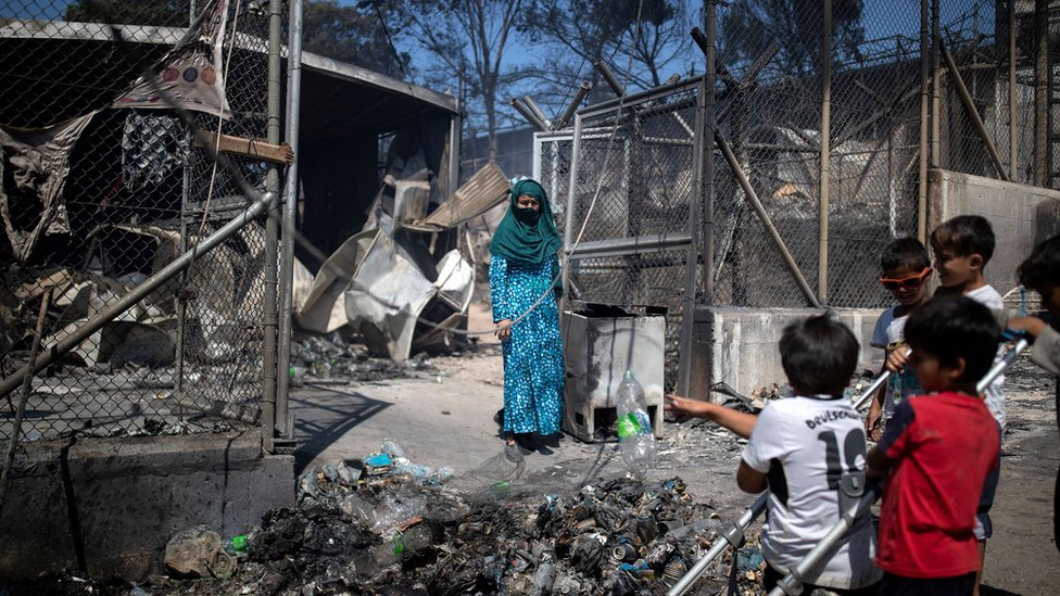 A woman stands next to destroyed shelters following a fire at the Moria camp for refugees and migrants on the island of Lesbos, Greece, 9 September 2020