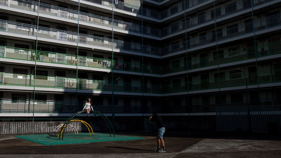 A woman poses for photographs in front of a public housing estate in Hong Kong on May 14, 2015.