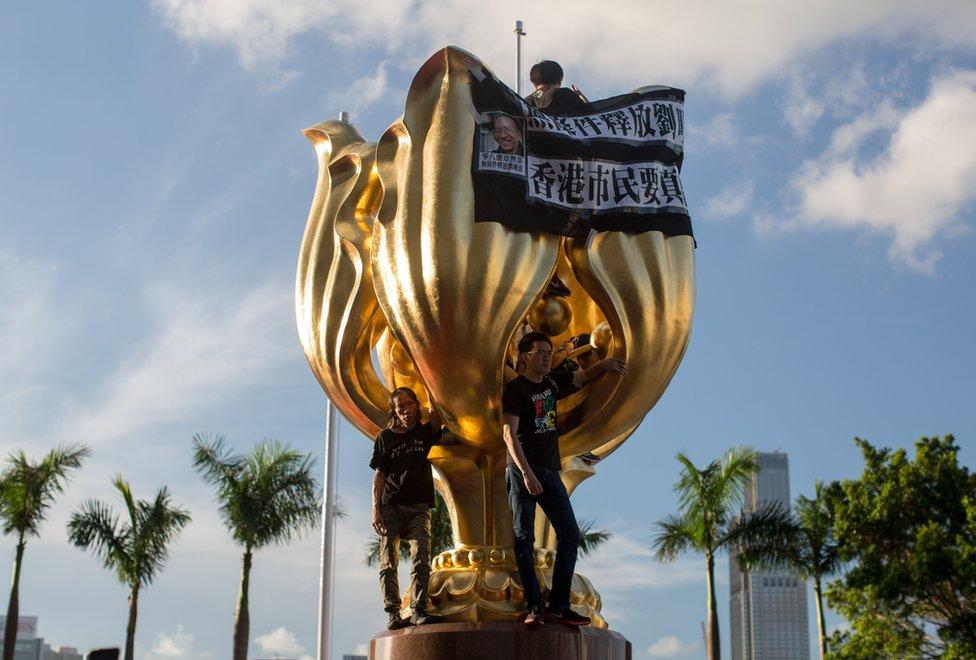 Manifestantes encadenados a una escultura en la plaza dorada de Bauhinia, 28 de junio de 2017