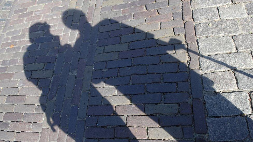 Sombra sobre piso de ladrillos y piedra.