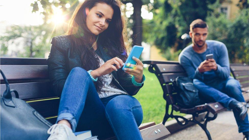 Dos personas utilizan sus teléfonos móviles en un parque