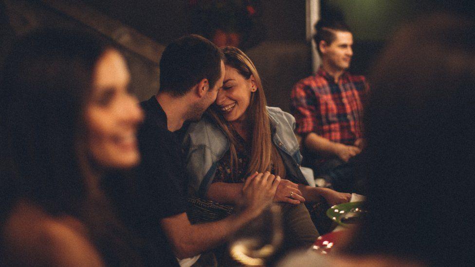 Una pareja coquetea en un ambiente social. Él tiene la mano sobre su mano y ella se está riendo.