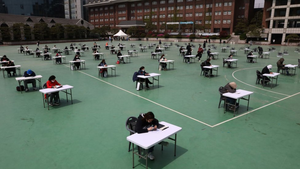 South Korean students wear masks and sit according to social distancing for an insurance planner examination at a playground in a Seoul university in April 2020