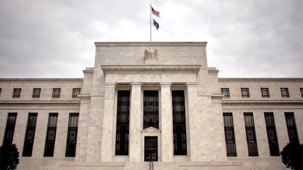 The US central bank, the Federal Reserve, keeps its key interest rate on hold but indicates it is more positive on the US economy.