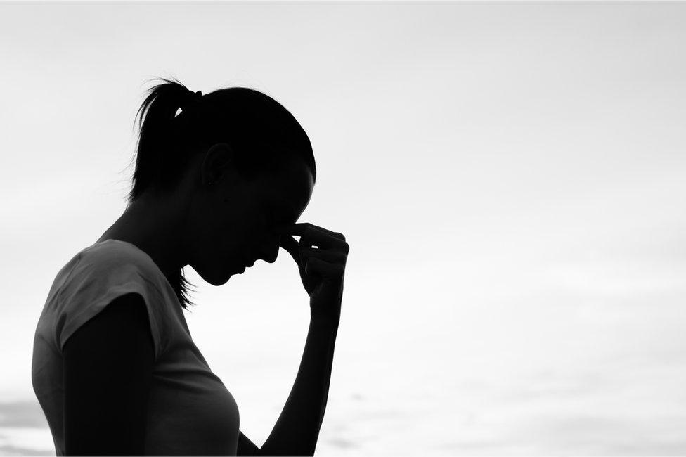 Silueta de una mujer agarrándose la cabeza