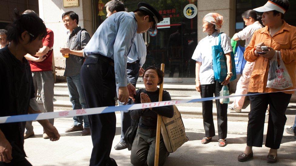 Una peticionaria china protestando frente a un policía.