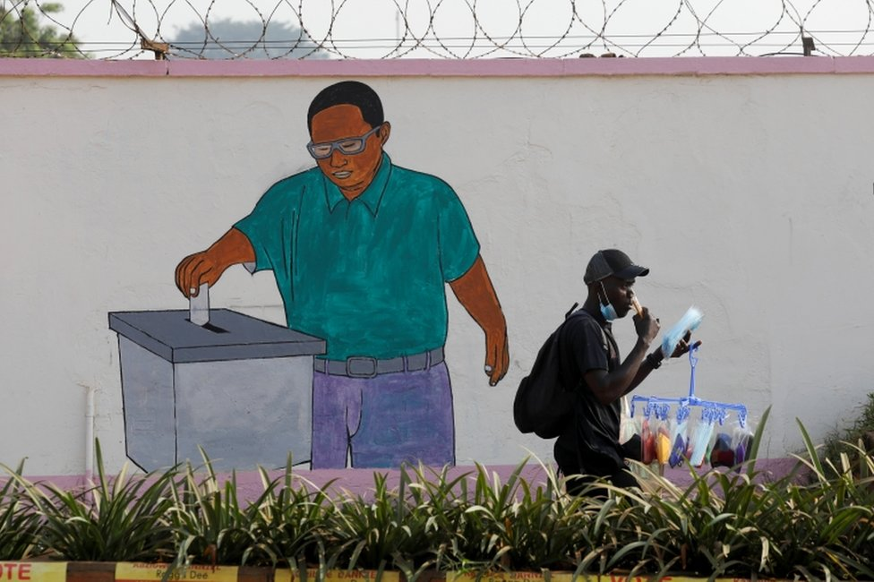 A man walks past a painting on the wall of the Ugandan electoral commission compound in Kampala.