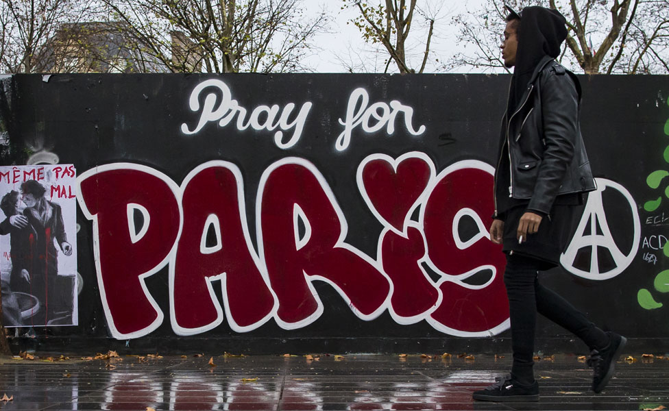 "A man walking in front of ""Pray for Paris"" graffiti"