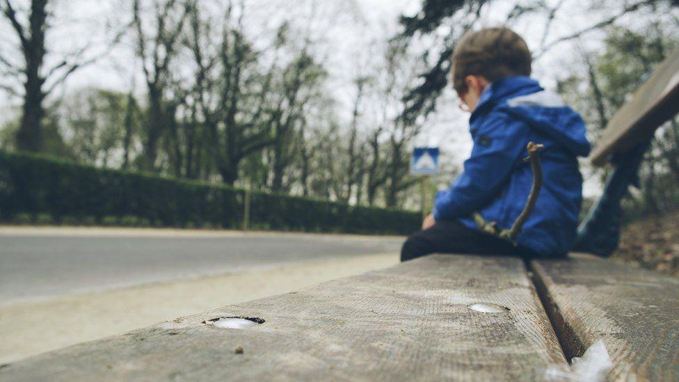 Niño sentado en un banco.