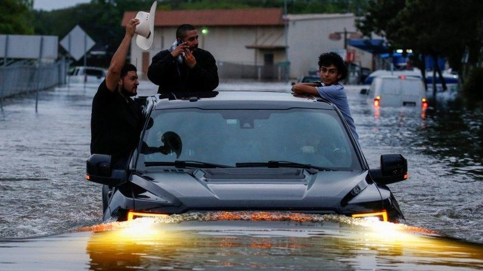 ثلاثة أشخاص في سيارة يحاولون عبور الشوارع الغارقة في مياه الفيضانات