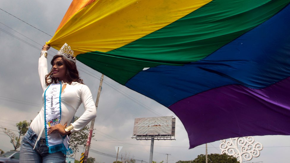 Una mujer lleva una bandera de varios colores