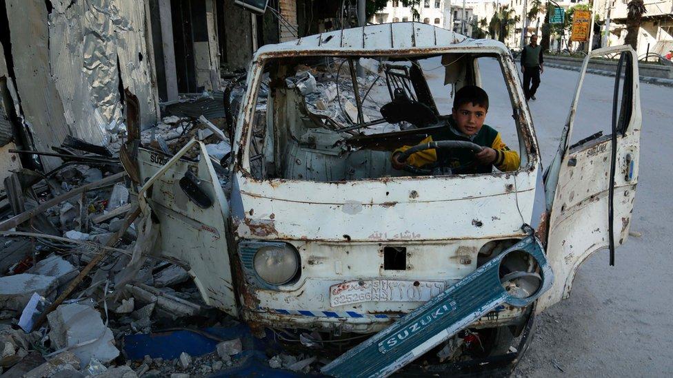 Niño juega dentro de un auto destrozado en Siria