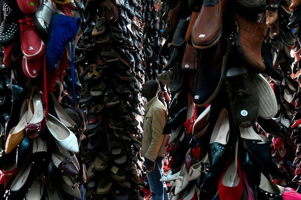 متسوق يستعرض، الأربعاء، مجموعة من الأحذية المصنوعة في الصين والمعروضة للبيع في العاصمة الكينية نيروبي.