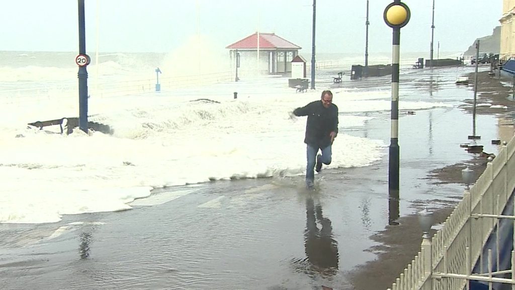 Huge waves crash over seafronts in Storm Brian surge