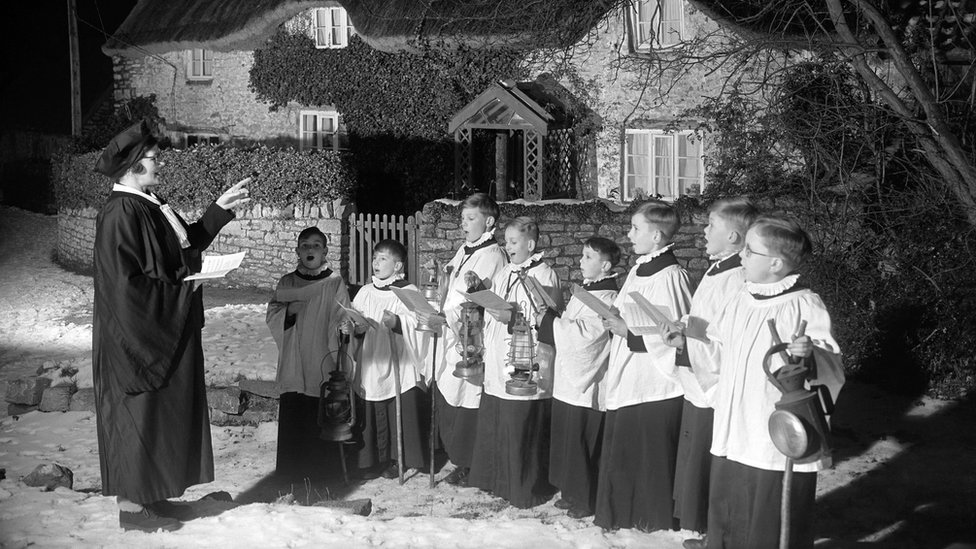 Choristers and choirmistress sing carols in the snow under a tree