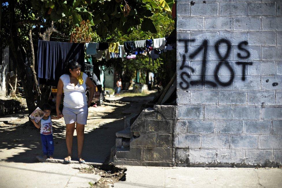 Mujer y niño junto a un grafiti del Barrio 18 en la colonia Valle del Sol en Apopa, El Salvador. (Foto: José Cabezas / Getty Images)