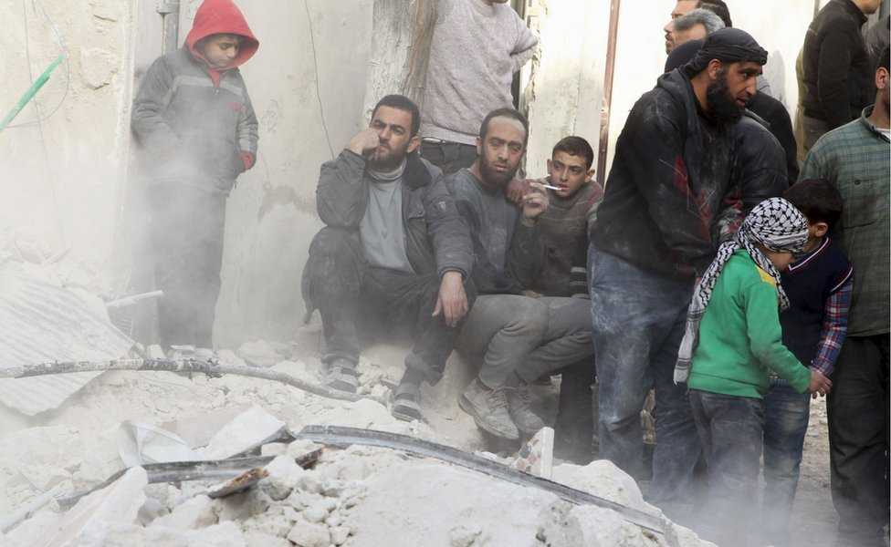 People sit on the rubble of a damaged building in Aleppo after air strikes by the Russian-Syrian government alliance