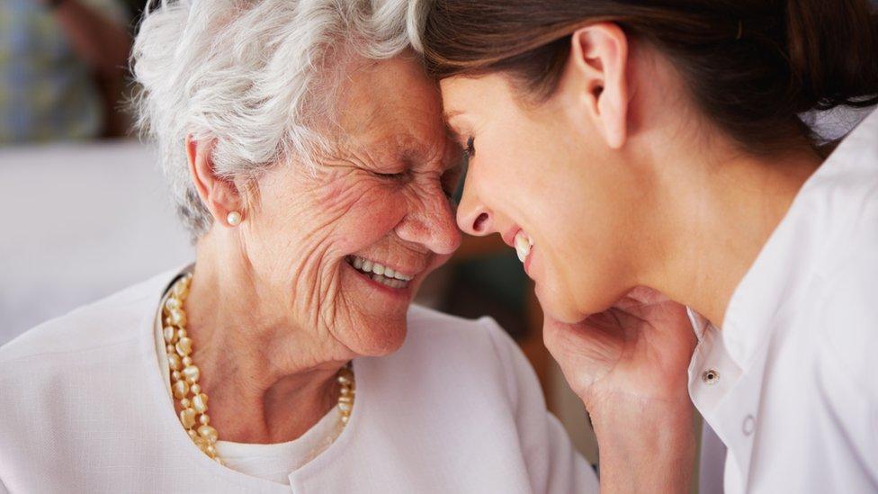 Anciana con chica sonriendo.